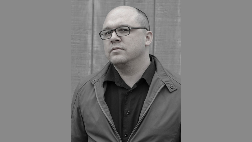 Matthew Olzmann in gray scale against a wood exterior. He wears glasses and his chin is titled up.