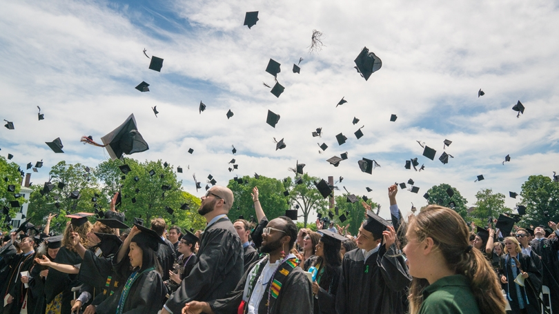 students tossing their graduation caps in the air
