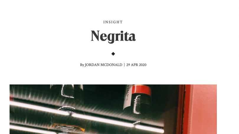 Text reading Negrita by Jordan McDonald. The bottom of the photo contains an image fragment of reflective glass